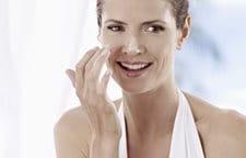 Donna che si applica la crema solare sul viso